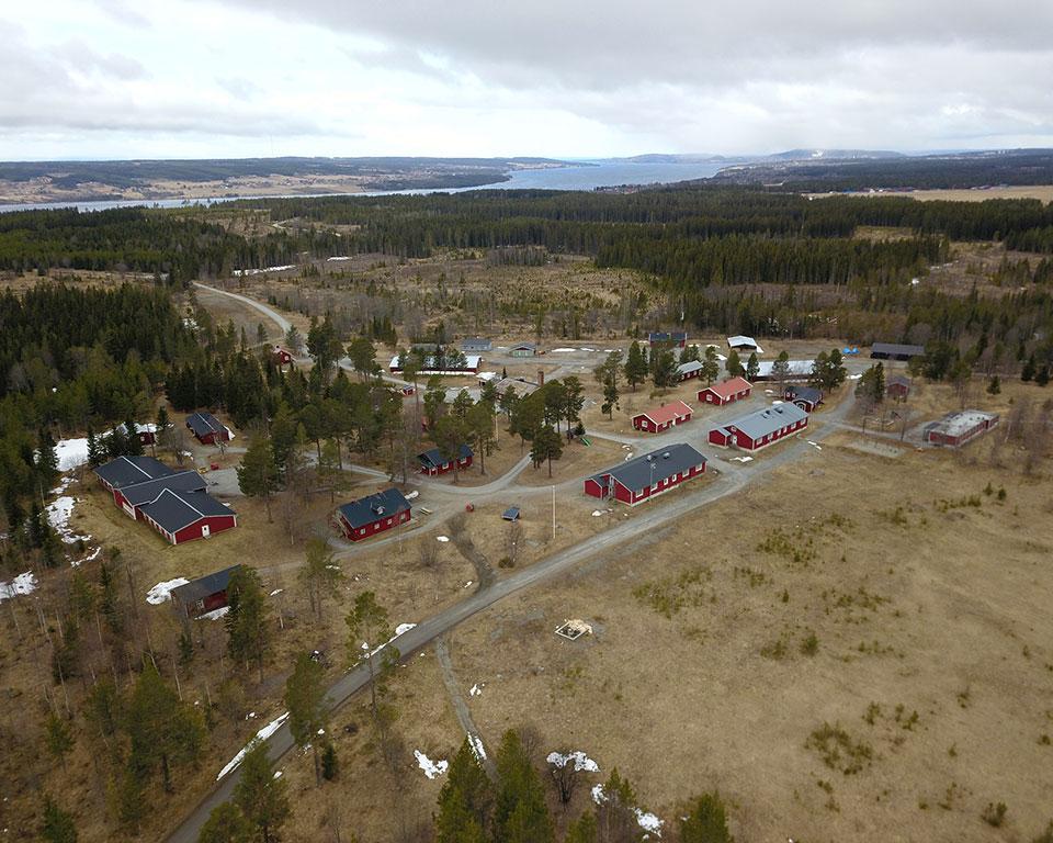 Översiktsbild med röda byggnader som är placerade på åkermark intill skog och hav.