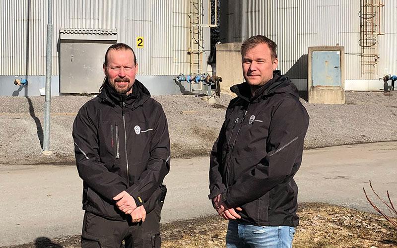 Två män står framför silos.