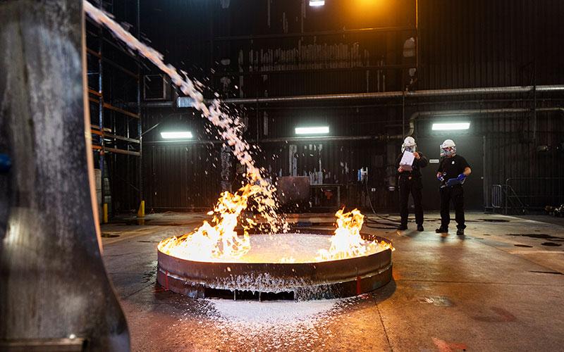 Smält stål hälls i beållare i industrilokal.