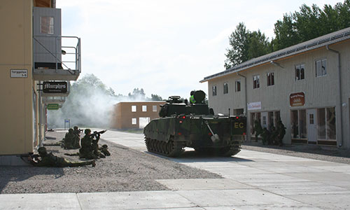 Stridsvagn kör genom svensk stad.