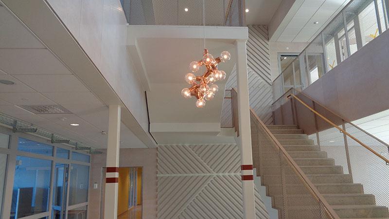 Hall med hög takhöjd och en trappa samt lampa i koppar och glas.
