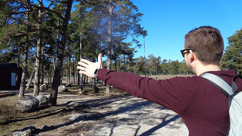Man pekar men båda armarna mot en skogsdunge.