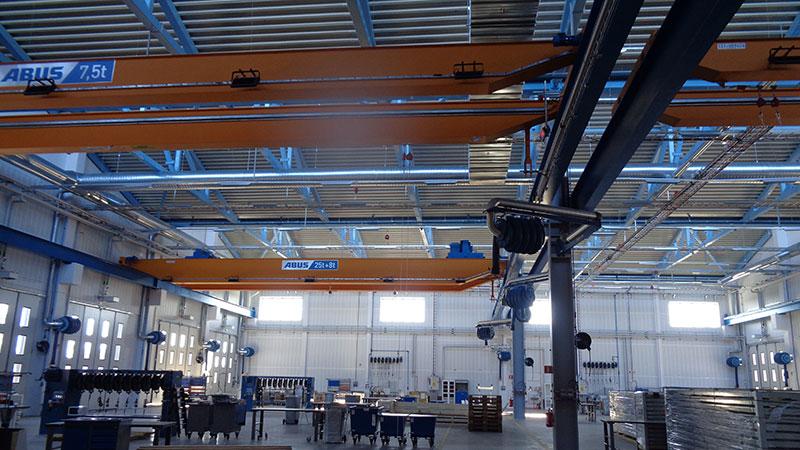 Verkstadsbyggnad med stålbjälkar, på golvet verktyg och maskiner.