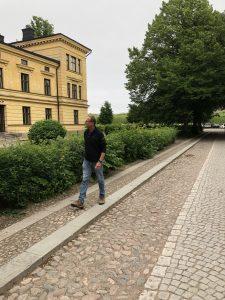 Man går på kullerstensgata framför en gammal husfasad.
