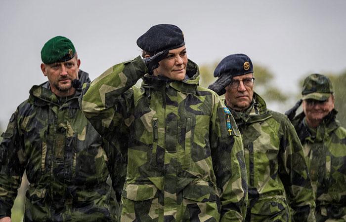 Kvinna i militäruniform gör givvakt.